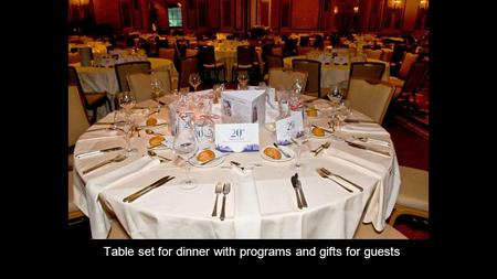 Table set for dinner with programs and gifts for guests.