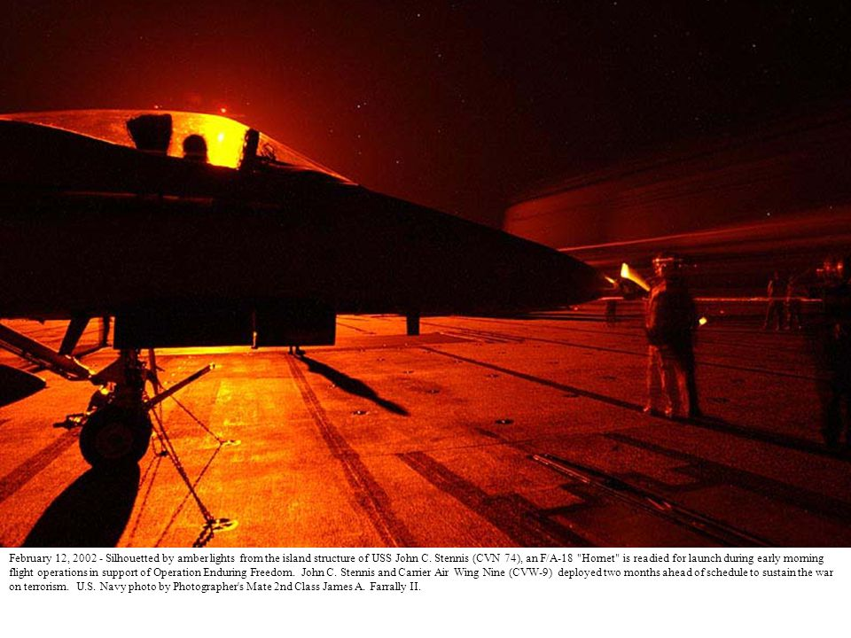 January 2, 2002 - As the sun rises an F-14 Tomcat from the Checkmates of Fighter Squadron Two One One (VF-211) goes to full after burner as it is launched from the flight deck of USS John C.
