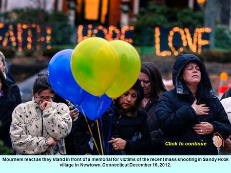 Mourners react as they stand in front of a memorial for victims of the recent mass shooting in Sandy Hook village in Newtown, Connecticut December 16,