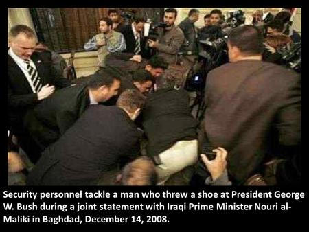 Security personnel tackle a man who threw a shoe at President George W. Bush during a joint statement with Iraqi Prime Minister Nouri al- Maliki in Baghdad,