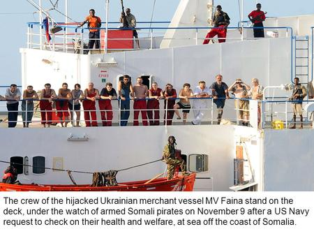 The crew of the hijacked Ukrainian merchant vessel MV Faina stand on the deck, under the watch of armed Somali pirates on November 9 after a US Navy request.