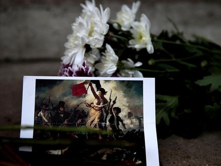 A postcard and flowers are left in tribute to victims of Paris attacks outside the French Embassy in London, Britain November 14, 2015. REUTERS/Suzanne.