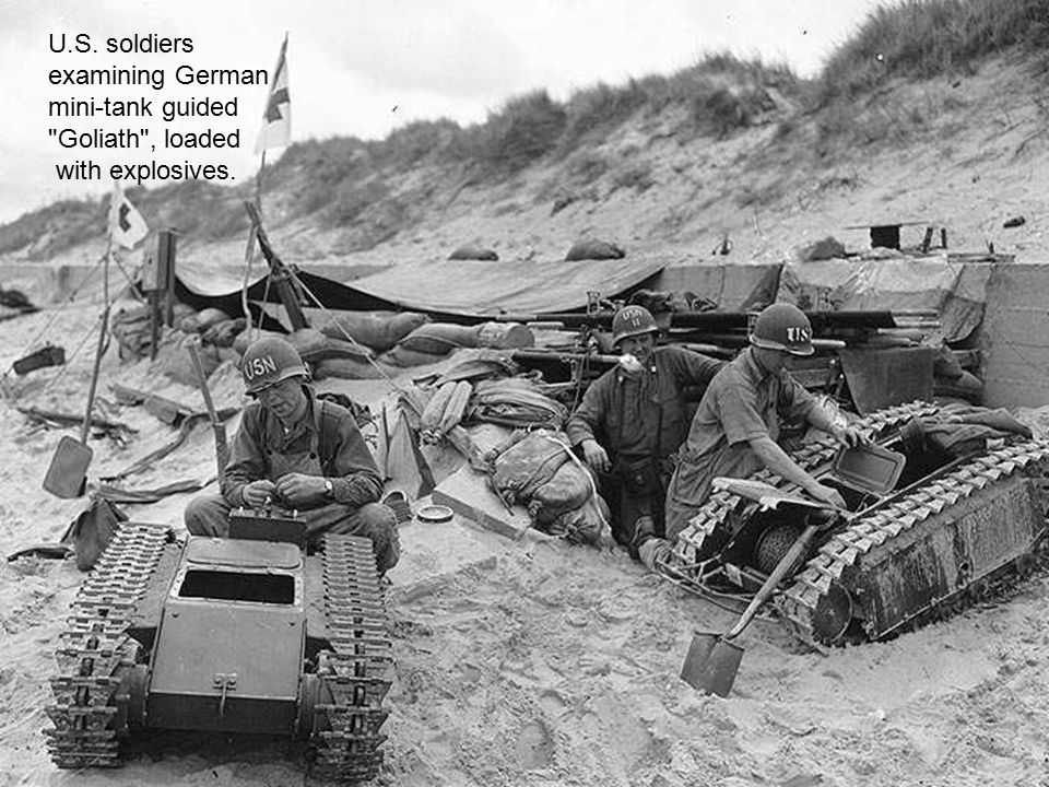 U.S. soldiers examining German mini-tank guided Goliath , loaded with explosives.