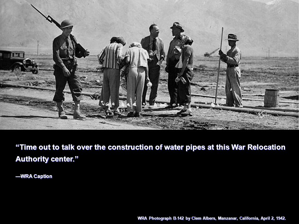 Residents of the Manzanar Center are shown waiting at the water hydrant for water for their barrack apartments.