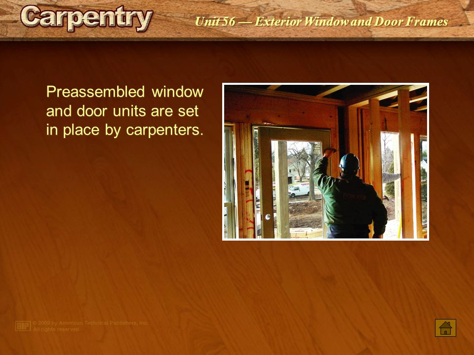 Preassembled window and door units are set in place by carpenters.