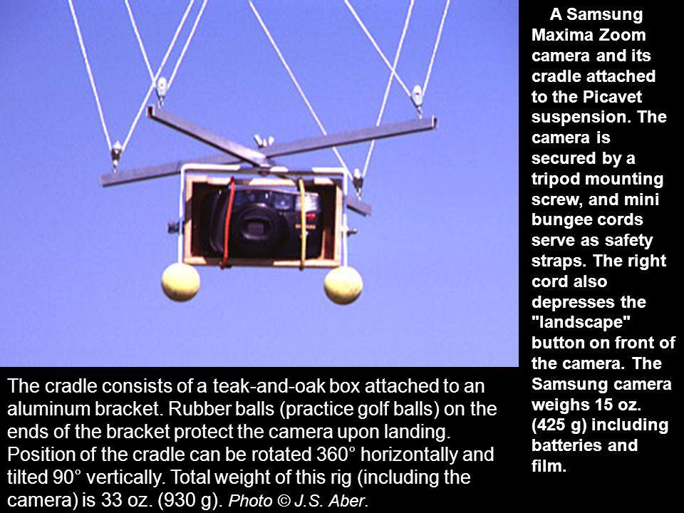 A Samsung Maxima Zoom camera and its cradle attached to the Picavet suspension. The camera is secured by a tripod mounting screw, and mini bungee cords serve as safety straps. The right cord also depresses the landscape button on front of the camera. The Samsung camera weighs 15 oz. (425 g) including batteries and film.