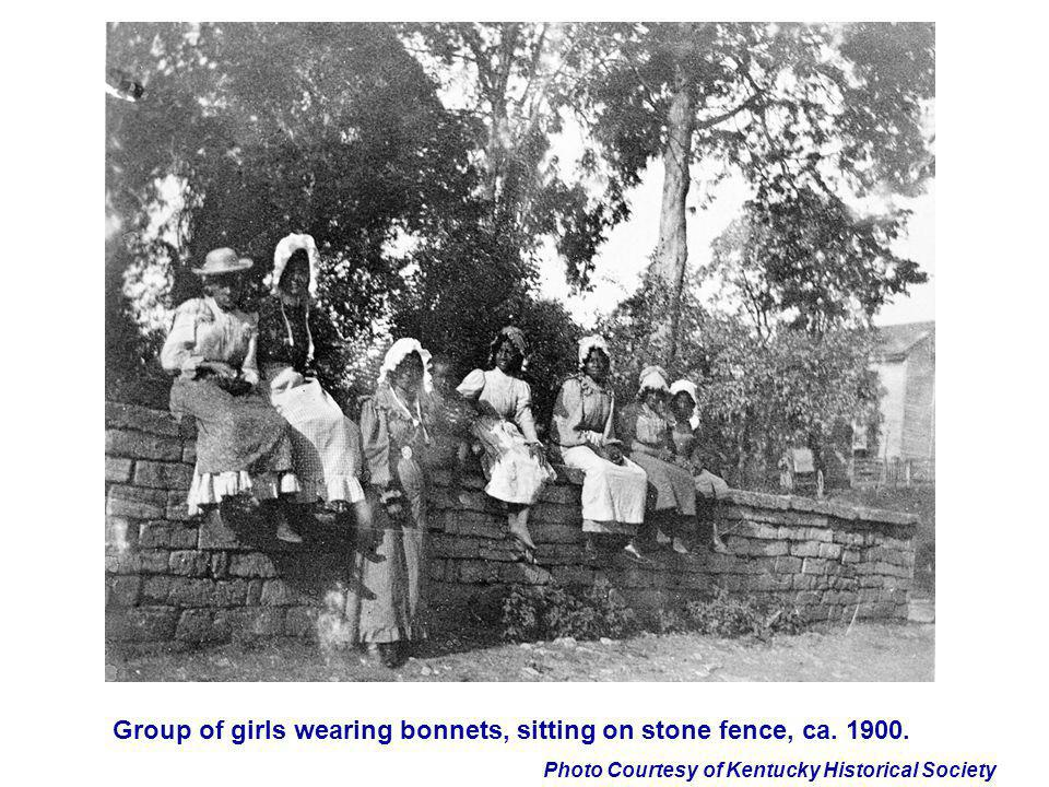 Group of girls wearing bonnets, sitting on stone fence, ca. 1900.