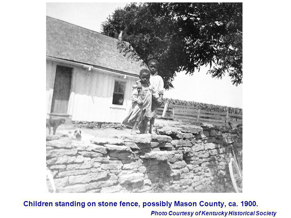 Children standing on stone fence, possibly Mason County, ca. 1900.
