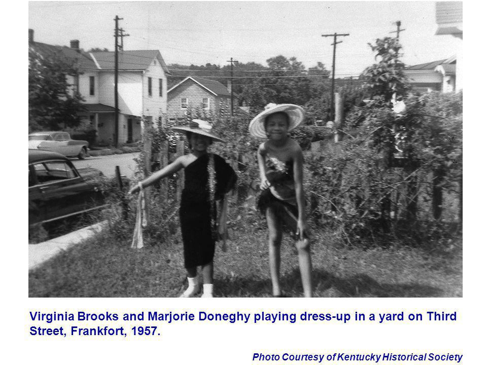 Virginia Brooks and Marjorie Doneghy playing dress-up in a yard on Third Street, Frankfort, 1957.