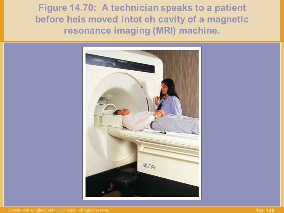 Figure 14.70: A technician speaks to a patient before heis moved intot eh cavity of a magnetic resonance imaging (MRI) machine.