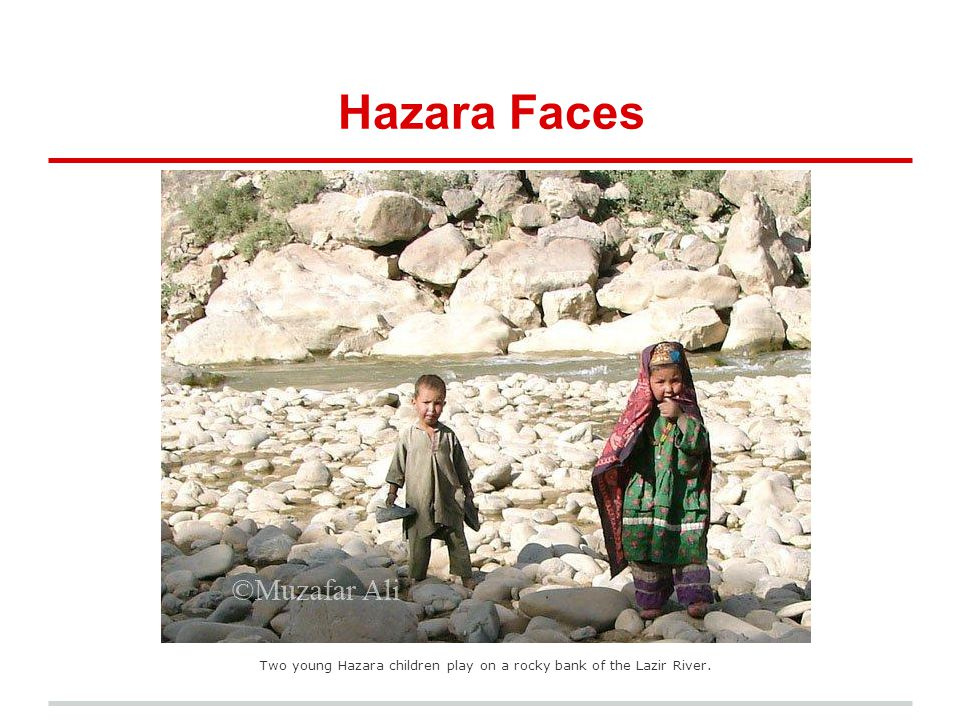 Two young Hazara children play on a rocky bank of the Lazir River.