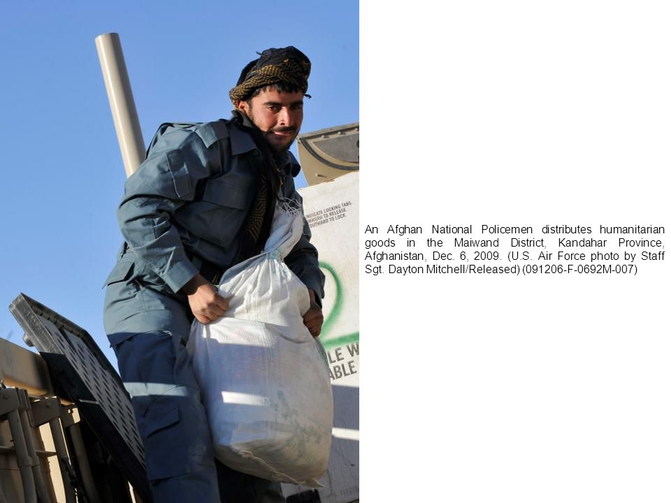 An Afghan National Policemen distributes humanitarian goods in the Maiwand District, Kandahar Province, Afghanistan, Dec.