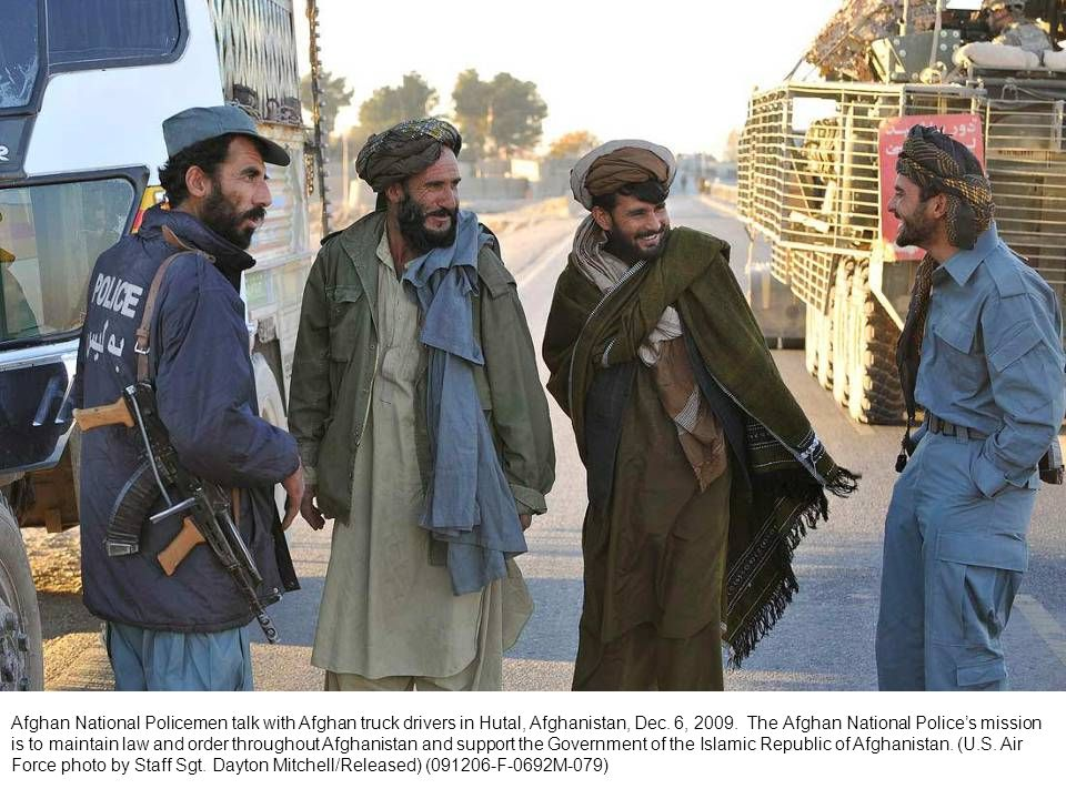 Afghan National Policemen talk with Afghan truck drivers in Hutal, Afghanistan, Dec.