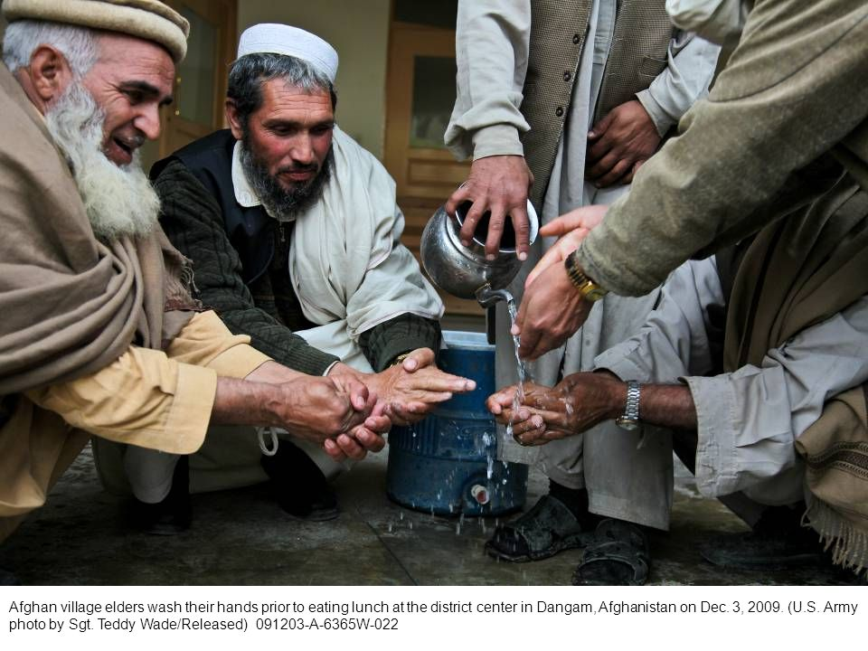 Afghan village elders wash their hands prior to eating lunch at the district center in Dangam, Afghanistan on Dec.