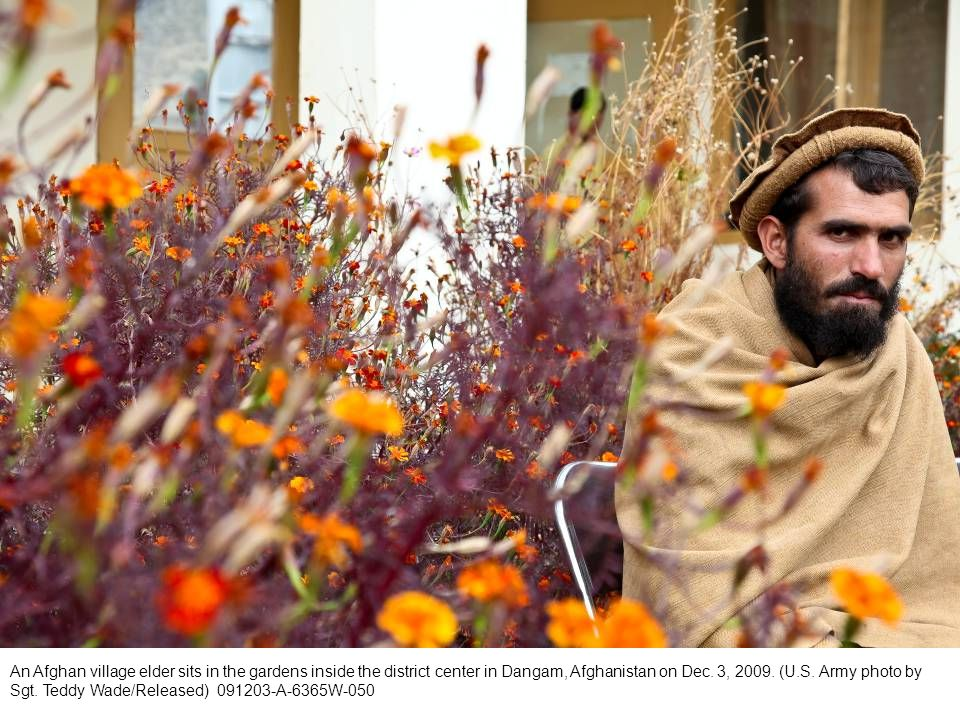 An Afghan village elder sits in the gardens inside the district center in Dangam, Afghanistan on Dec.
