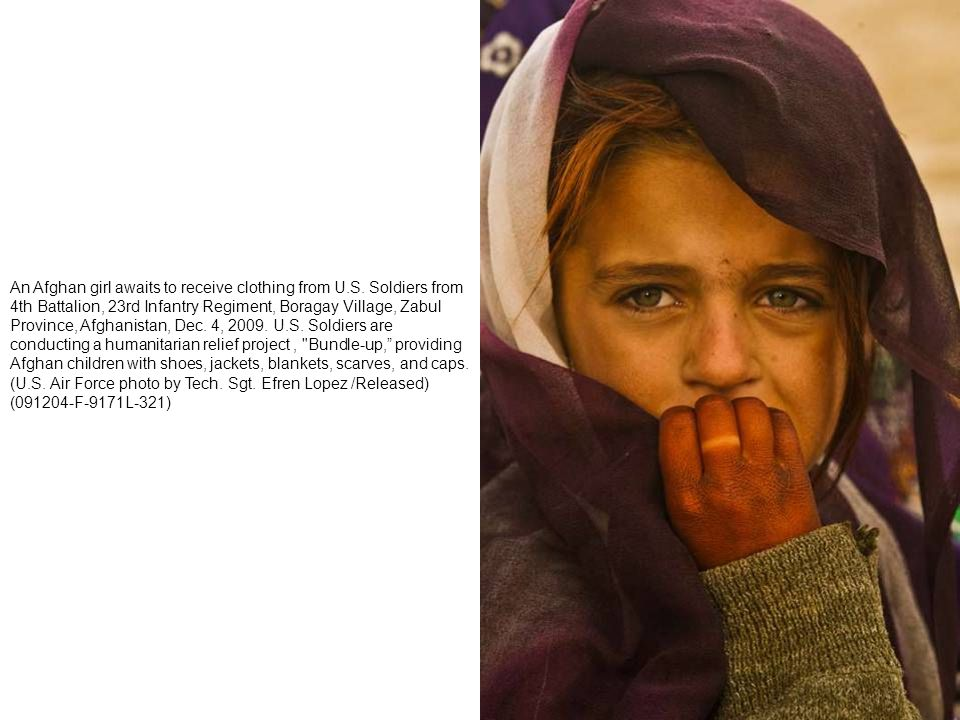 An Afghan girl awaits to receive clothing from U. S