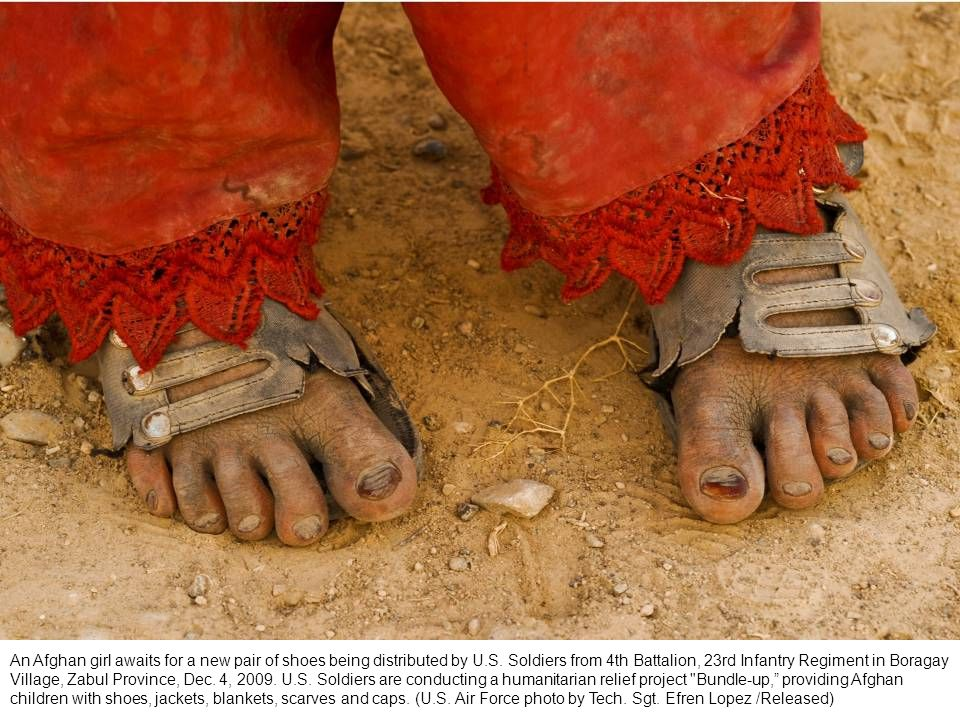 An Afghan girl awaits for a new pair of shoes being distributed by U.S.