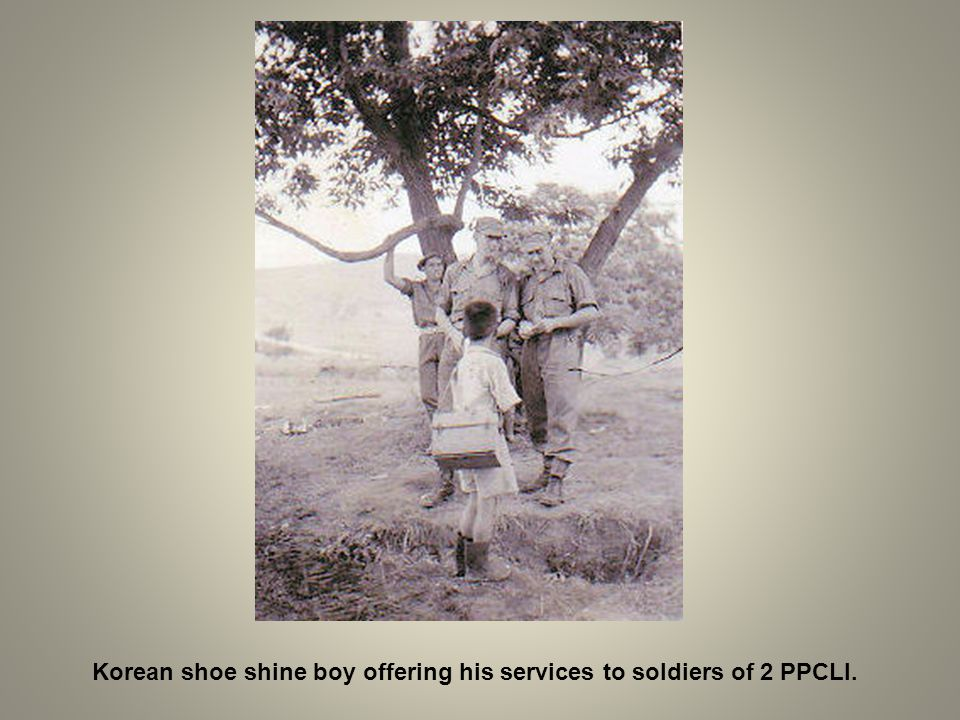 Korean shoe shine boy offering his services to soldiers of 2 PPCLI.