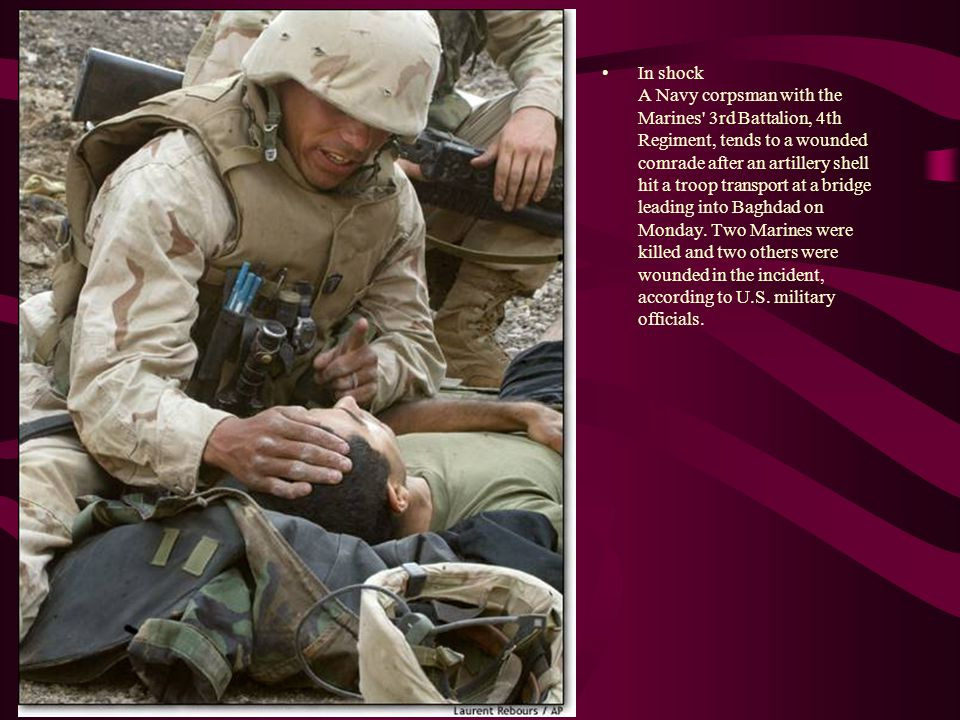 In shock A Navy corpsman with the Marines 3rd Battalion, 4th Regiment, tends to a wounded comrade after an artillery shell hit a troop transport at a bridge leading into Baghdad on Monday.
