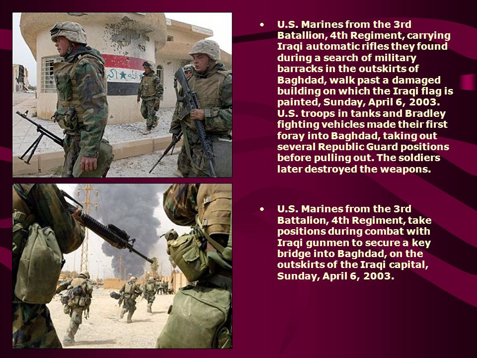 U.S. Marines from the 3rd Batallion, 4th Regiment, carrying Iraqi automatic rifles they found during a search of military barracks in the outskirts of Baghdad, walk past a damaged building on which the Iraqi flag is painted, Sunday, April 6, 2003. U.S. troops in tanks and Bradley fighting vehicles made their first foray into Baghdad, taking out several Republic Guard positions before pulling out. The soldiers later destroyed the weapons.