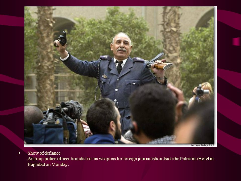 Show of defiance An Iraqi police officer brandishes his weapons for foreign journalists outside the Palestine Hotel in Baghdad on Monday.