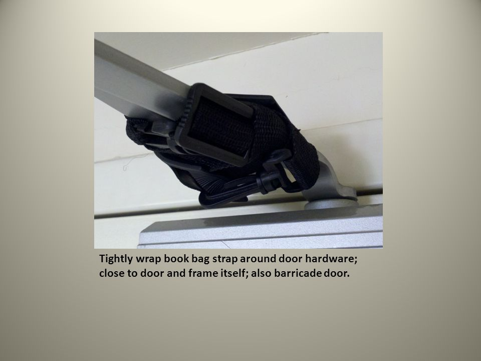Tightly wrap book bag strap around door hardware; close to door and frame itself; also barricade door.