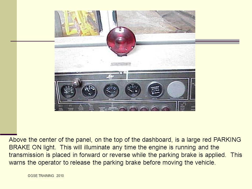 Above the center of the panel, on the top of the dashboard, is a large red PARKING BRAKE ON light. This will illuminate any time the engine is running and the transmission is placed in forward or reverse while the parking brake is applied. This warns the operator to release the parking brake before moving the vehicle.