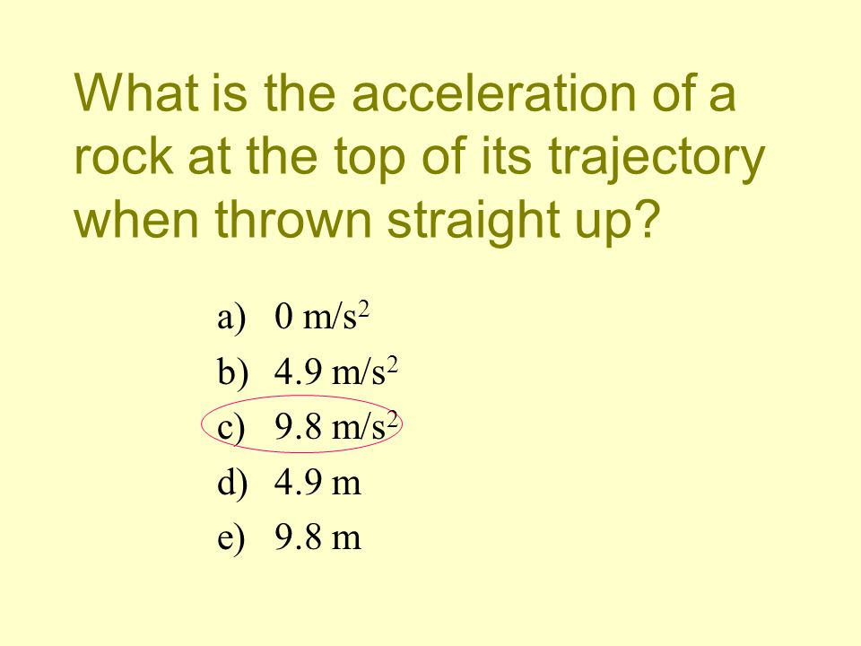 What is the acceleration of a rock at the top of its trajectory when thrown straight up