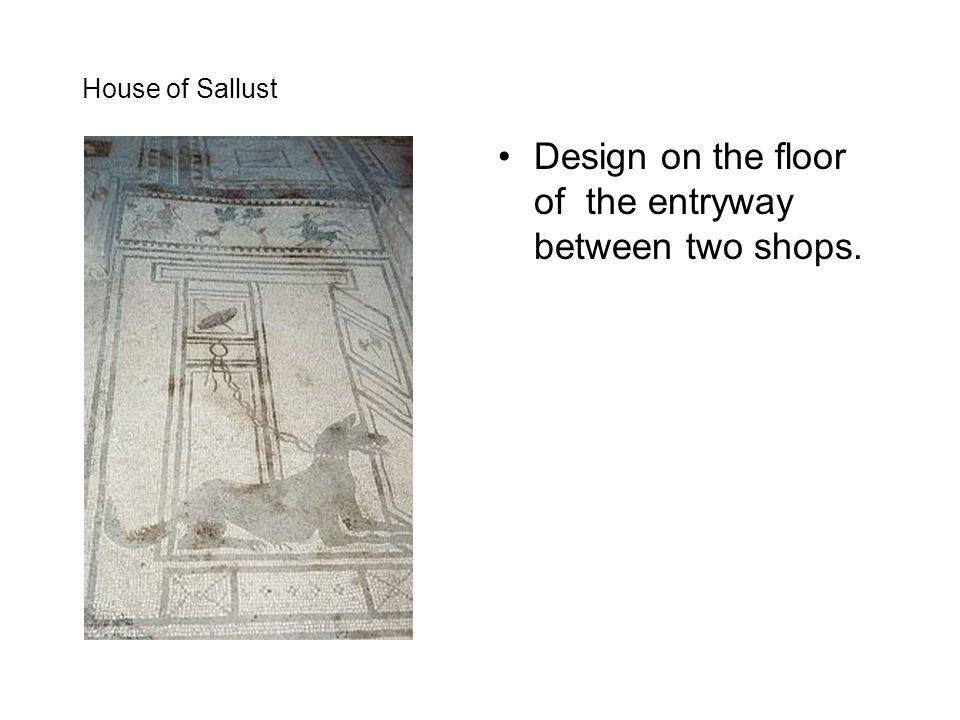 Design on the floor of the entryway between two shops.