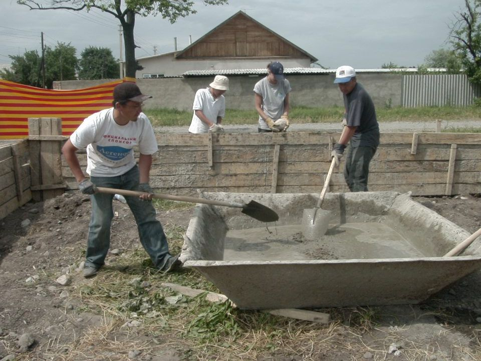 Volunteers preparing the cement for the foundations
