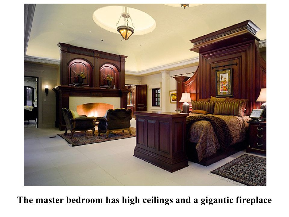 The master bedroom has high ceilings and a gigantic fireplace