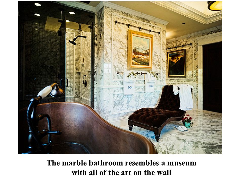 The marble bathroom resembles a museum with all of the art on the wall