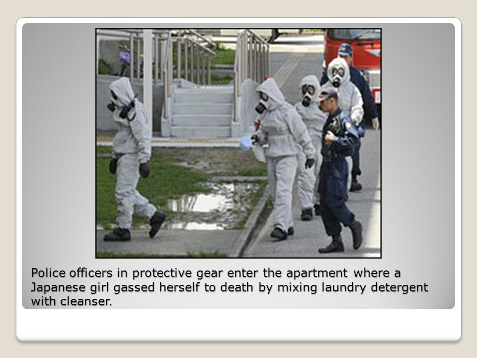 Police officers in protective gear enter the apartment where a Japanese girl gassed herself to death by mixing laundry detergent with cleanser.