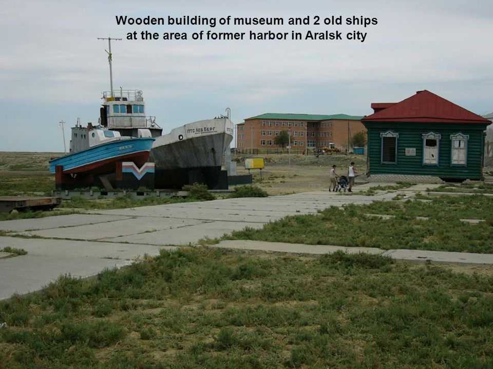 Wooden building of museum and 2 old ships at the area of former harbor in Aralsk city