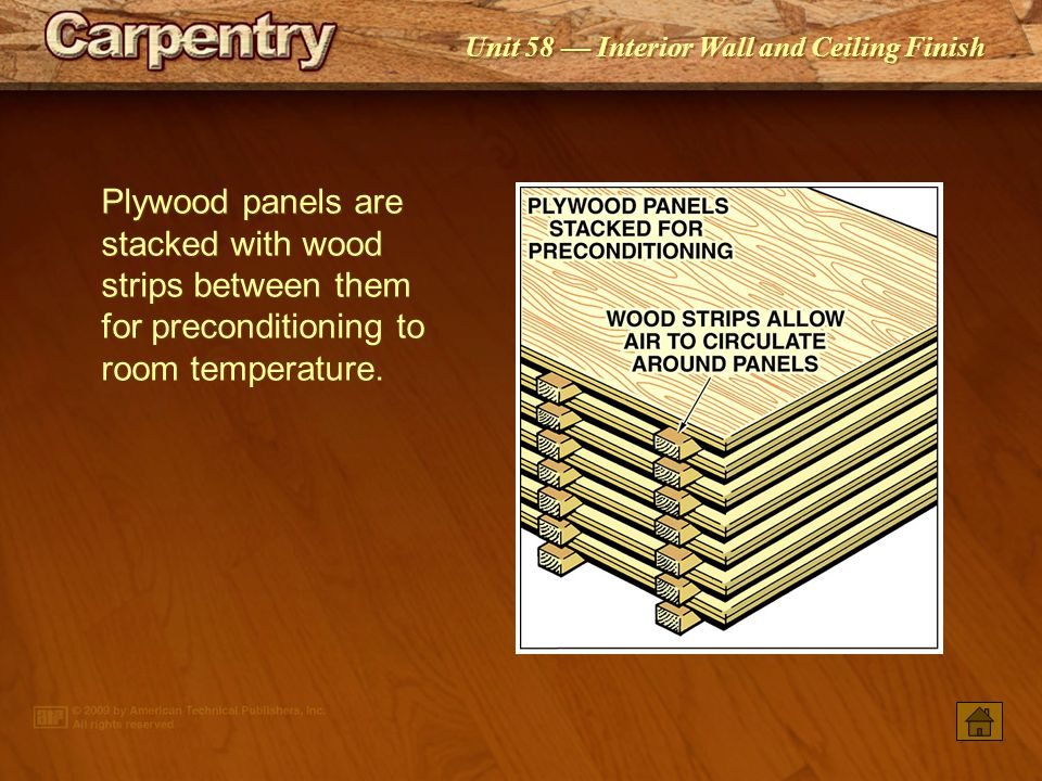 Plywood panels are stacked with wood strips between them for preconditioning to room temperature.