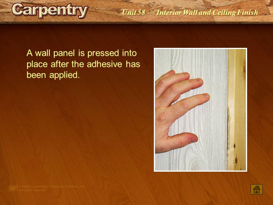 A wall panel is pressed into place after the adhesive has been applied.