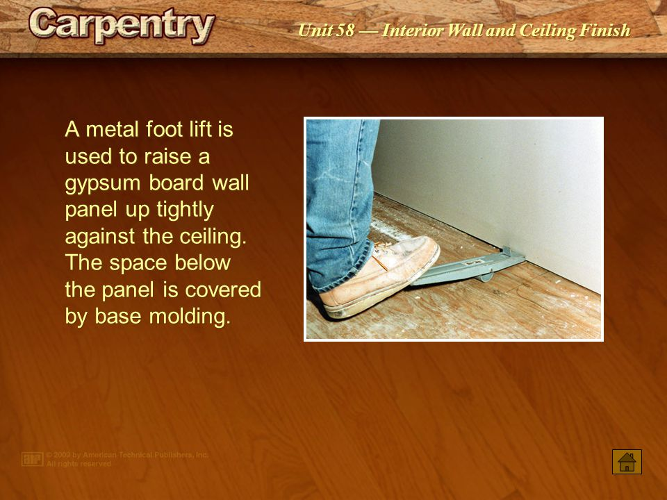 A metal foot lift is used to raise a gypsum board wall panel up tightly against the ceiling. The space below the panel is covered by base molding.