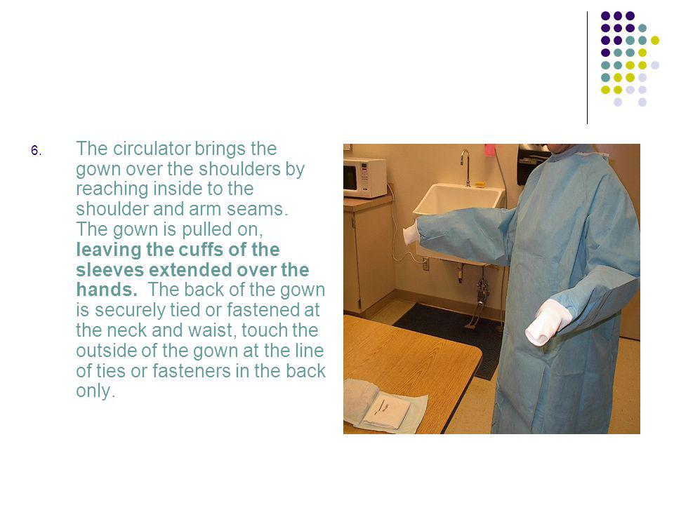 The circulator brings the gown over the shoulders by reaching inside to the shoulder and arm seams.