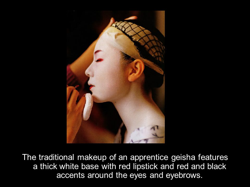 The traditional makeup of an apprentice geisha features a thick white base with red lipstick and red and black accents around the eyes and eyebrows.