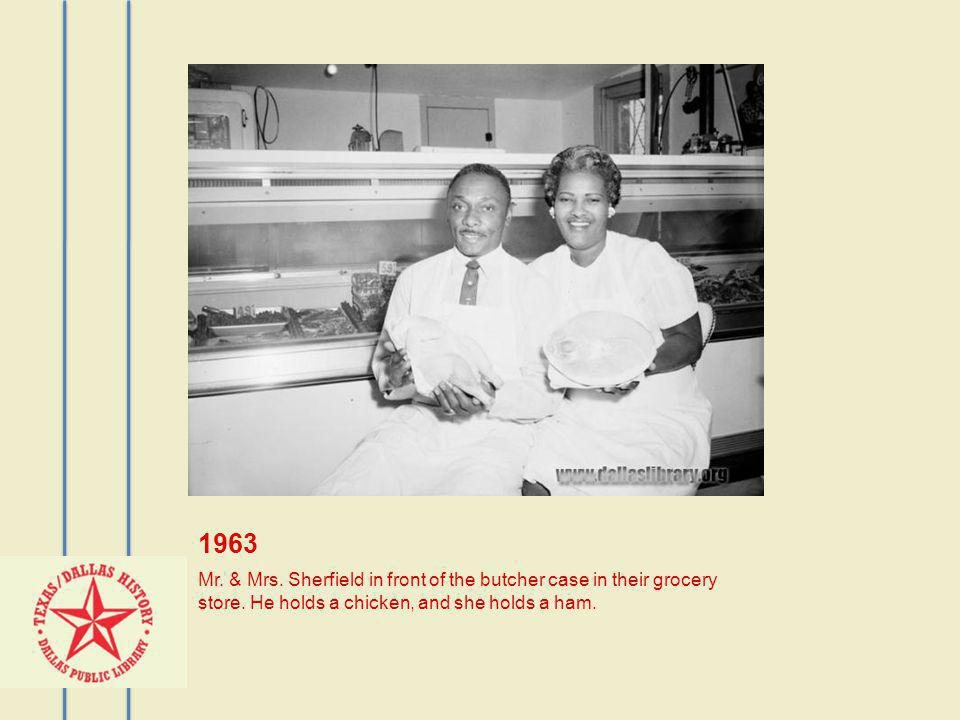 1963 Mr. & Mrs. Sherfield in front of the butcher case in their grocery store.