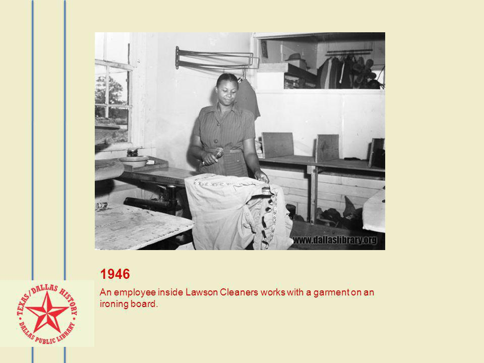 1946 An employee inside Lawson Cleaners works with a garment on an ironing board.