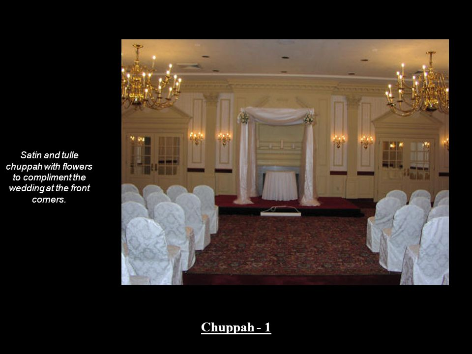 Satin and tulle chuppah with flowers to compliment the wedding at the front corners.