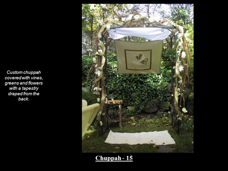 Custom chuppah covered with vines, greens and flowers with a tapestry draped from the back.