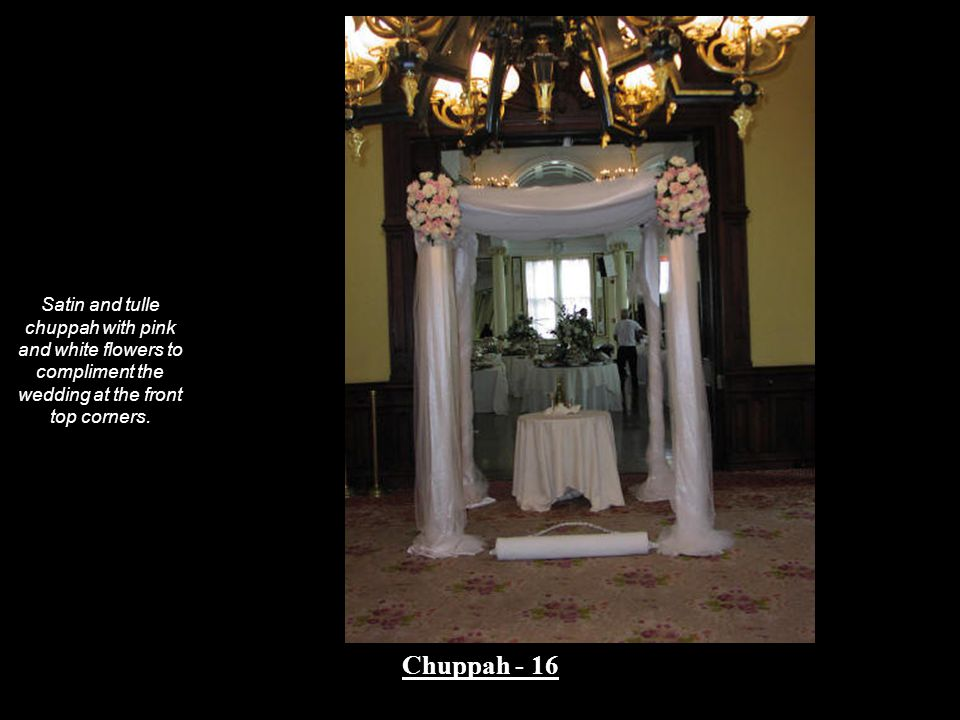 Satin and tulle chuppah with pink and white flowers to compliment the wedding at the front top corners.