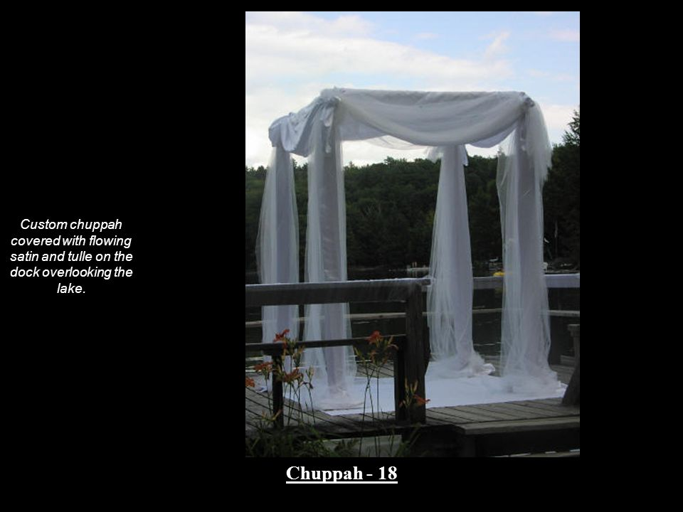 Custom chuppah covered with flowing satin and tulle on the dock overlooking the lake.
