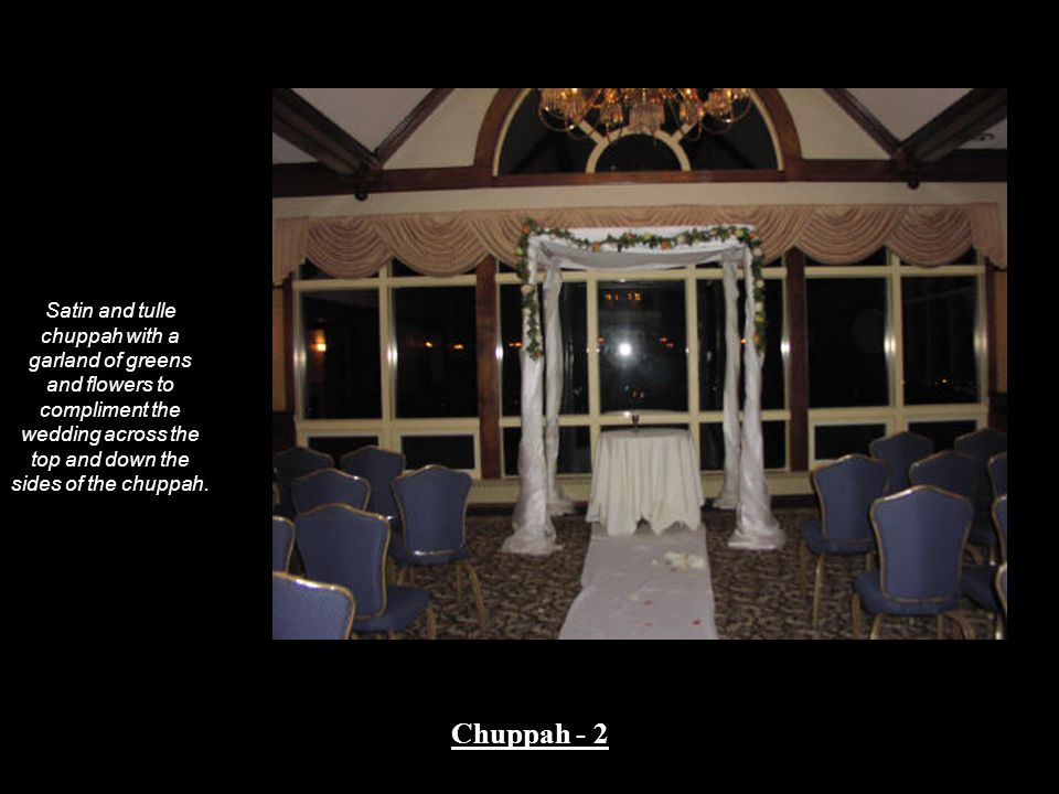 Satin and tulle chuppah with a garland of greens and flowers to compliment the wedding across the top and down the sides of the chuppah.