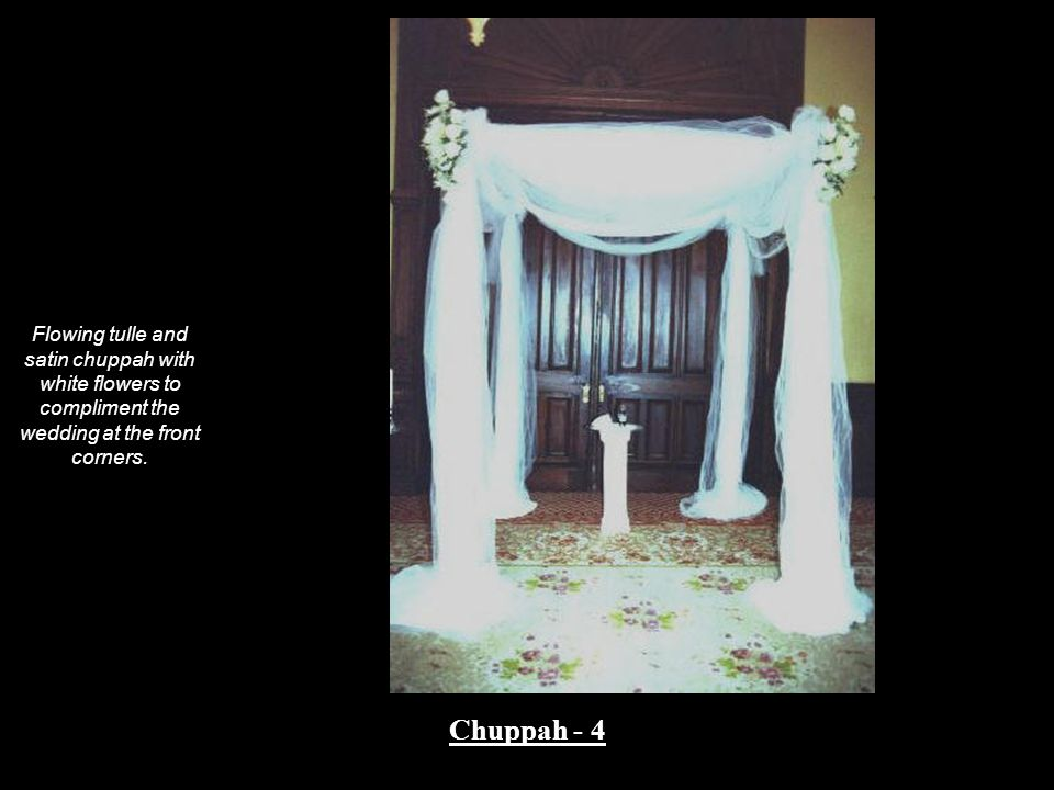 Flowing tulle and satin chuppah with white flowers to compliment the wedding at the front corners.