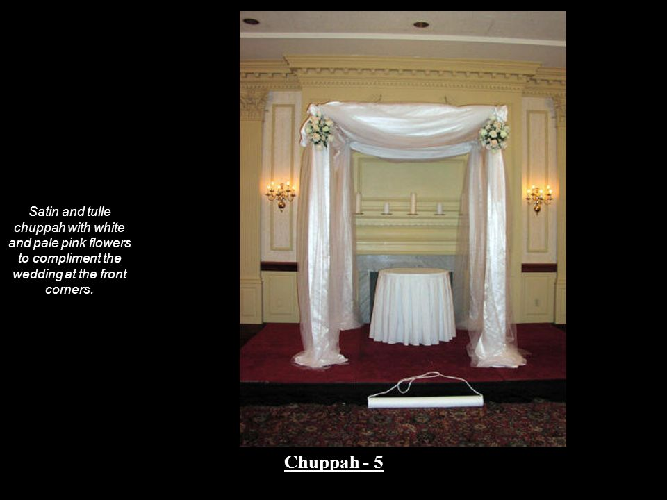 Satin and tulle chuppah with white and pale pink flowers to compliment the wedding at the front corners.