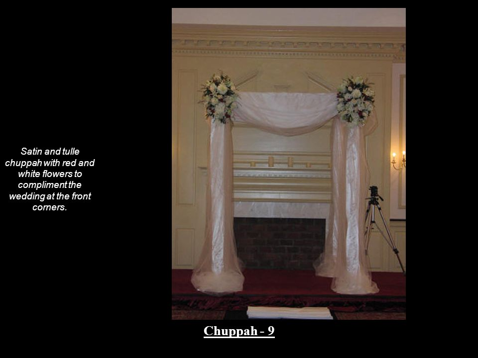 Satin and tulle chuppah with red and white flowers to compliment the wedding at the front corners.