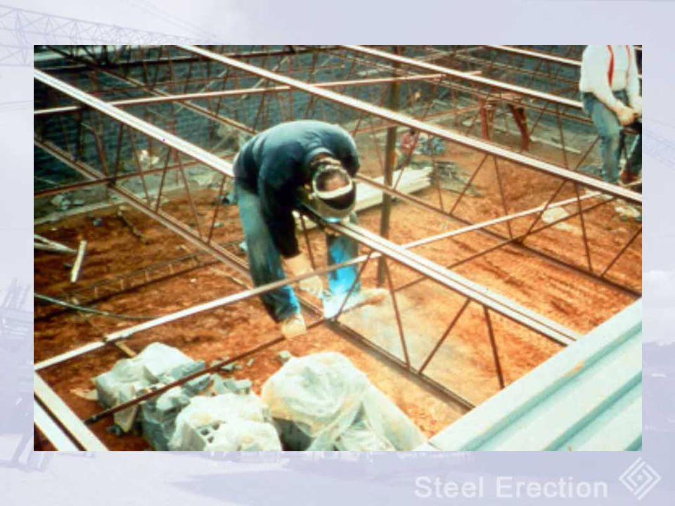 Ironworker welding horizontal bridging for joists